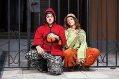 Pares jovenes del hippie que se sientan en la acera Fotografía de archivo libre de regalías