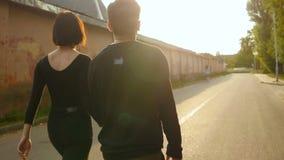 Pares jovenes del hombre y de la mujer que caminan en el puente en el verano Luz de la puesta del sol Pares felices elegantes que almacen de video