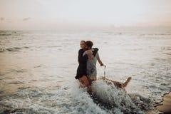 Pares jovenes del inconformista de la risa feliz hermosa con golden retriever en la playa océano una arena Ondas concepte de la l imagen de archivo libre de regalías