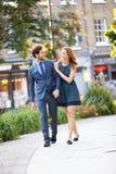 Pares jovenes del negocio que caminan a través de parque de la ciudad junto Fotos de archivo