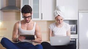 Pares jovenes del negocio que trabajan con el ordenador portátil en casa en cocina El concepto de negocio casero, independiente almacen de metraje de vídeo