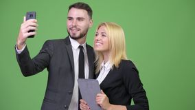 Pares jovenes del negocio usando la tableta digital mientras que toma el selfie junto metrajes