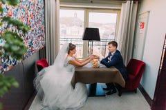Pares jovenes del recién casado que se sientan junto en restaurante en la tabla para dos con el ramo nupcial de rosas que ponen e Foto de archivo libre de regalías