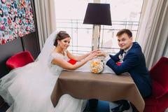 Pares jovenes del recién casado que se sientan junto en restaurante por la ventana en la tabla para dos con el ramo nupcial de co Fotos de archivo