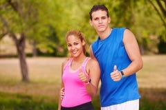 Pares jovenes del retrato con el pulgar para arriba que hace los deportes que entrenan a Fitnes Fotos de archivo libres de regalías