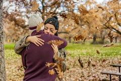 Pares jovenes del retrato que abrazan en una lluvia de hojas en otoño CCB Foto de archivo