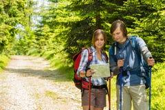 Pares jovenes del senderismo que comprueban el mapa Imagen de archivo