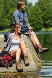 Pares jovenes del senderismo que descansan en la orilla del lago Foto de archivo libre de regalías