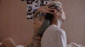 Pares jovenes del tatuaje en casa en la cama