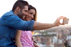 Pares jovenes del turista en ciudad usando el teléfono móvil Fotos de archivo