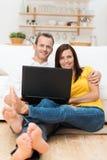 Pares jovenes descalzos que se relajan con un ordenador portátil Foto de archivo