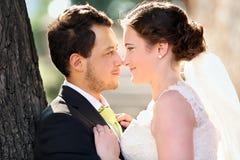 Pares jovenes después de casarse en un abrazo cara a cara Fotos de archivo