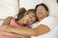 Pares jovenes dormidos en cama Fotografía de archivo libre de regalías