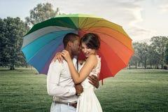 Pares jovenes dulces debajo de un paraguas colorido Imagen de archivo