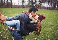Pares jovenes dulces que comparten un beso mientras que una fecha Imágenes de archivo libres de regalías