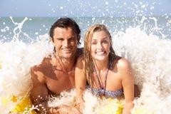 Pares jovenes el día de fiesta de la playa Imagen de archivo