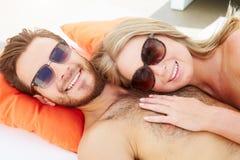 Pares jovenes el día de fiesta que se relaja por la piscina Foto de archivo
