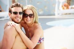 Pares jovenes el día de fiesta que se relaja por la piscina Imagen de archivo