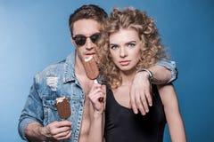 Pares jovenes elegantes en el amor que se coloca de abarcamiento y que sostiene del helado Fotografía de archivo