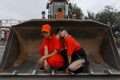 Pares jovenes elegantes en ropa anaranjada de moda con el casquillo fotografía de archivo libre de regalías