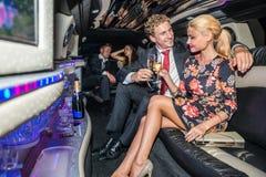 Pares jovenes elegantes que tuestan las flautas de champán en limusina Foto de archivo libre de regalías