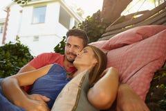Pares jovenes elogiosos que se relajan en una hamaca junto Fotos de archivo libres de regalías