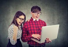 Pares jovenes emocionados con triunfo usando el ordenador portátil fotografía de archivo