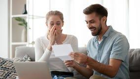 Pares jovenes emocionados felices que reciben buenas noticias inesperadas imagenes de archivo