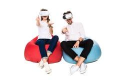 Pares jovenes emocionados que experimentan la realidad virtual asentada en los beanbags aislados en el fondo blanco Fotos de archivo libres de regalías