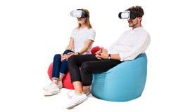 Pares jovenes emocionados que experimentan la realidad virtual asentada en los beanbags aislados en el fondo blanco Imagen de archivo libre de regalías