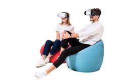Pares jovenes emocionados que experimentan la realidad virtual asentada en los beanbags aislados en el fondo blanco Fotografía de archivo