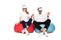 Pares jovenes emocionados que experimentan la realidad virtual asentada en los beanbags aislados en el fondo blanco Fotografía de archivo libre de regalías