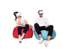Pares jovenes emocionados que experimentan la realidad virtual asentada en los beanbags aislados en el fondo blanco Imagen de archivo