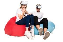 Pares jovenes emocionados que experimentan la realidad virtual asentada en los beanbags aislados en el fondo blanco Fotos de archivo