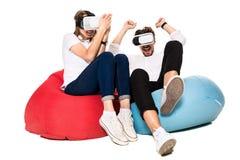 Pares jovenes emocionados que experimentan la realidad virtual asentada en los beanbags aislados en el fondo blanco Imagenes de archivo