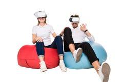 Pares jovenes emocionados que experimentan la realidad virtual asentada en los beanbags aislados en el fondo blanco Foto de archivo