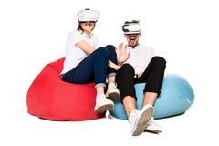 Pares jovenes emocionados que experimentan la realidad virtual asentada en los beanbags aislados en el fondo blanco Imágenes de archivo libres de regalías