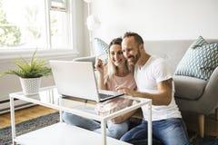 Pares jovenes emocionados que hacen compras en línea, sosteniendo la tarjeta de crédito y mirando el ordenador portátil en casa imágenes de archivo libres de regalías