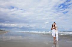 Pares jovenes en abrazo romántico en la playa fotos de archivo libres de regalías
