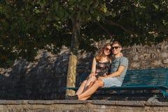 Pares jovenes en amor asentados en un banco y la relajaci?n durante un d?a soleado imagen de archivo