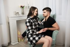 Pares jovenes en amor en casa en la butaca Fotografía de archivo libre de regalías