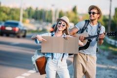 pares jovenes en amor con la cartulina vacía que hace autostop mientras que Imagen de archivo libre de regalías