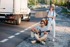 pares jovenes en amor con la cartulina vacía que hace autostop mientras que Foto de archivo libre de regalías