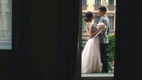 Pares jovenes en amor con los recienes casados que se colocan en el balcón blanco y que llevan a cabo las manos, vista posterior metrajes