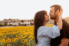 Pares jovenes en amor en el campo del girasol en la puesta del sol imágenes de archivo libres de regalías