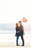 Pares jovenes en amor, en la orilla, con un globo rojo Fotografía de archivo