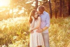 Pares jovenes en amor en la puesta del sol en el campo Imágenes de archivo libres de regalías