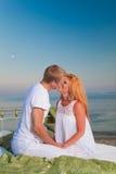 Pares jovenes en amor en una cama en la playa Imagenes de archivo