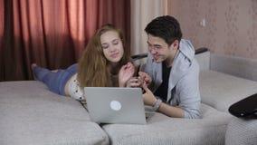 Pares jovenes en amor usando el ordenador portátil Tecnología, familia, concepto del comercio electrónico metrajes