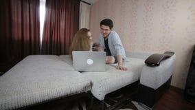 Pares jovenes en amor usando el ordenador portátil Tecnología, familia, concepto del comercio electrónico almacen de metraje de vídeo